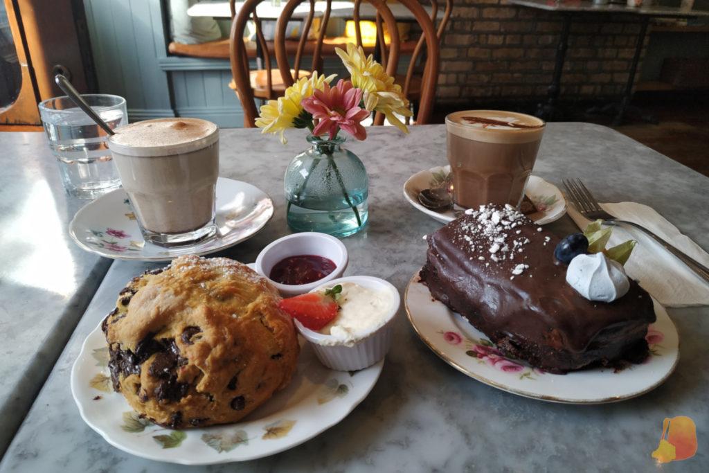 Desayuno con un Chai Latte, un scone, un café y una tarta de chocolate